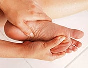 Image of person rubbing bottom of feet suffering from foot arch pain