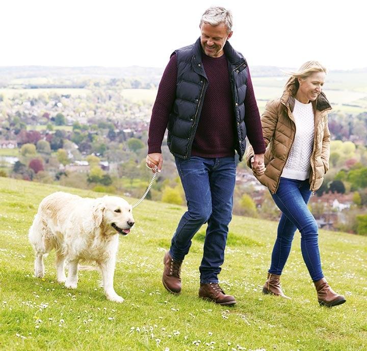 image of older couple walking their dog
