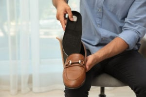 image of man inserting an insole into a dress shoe