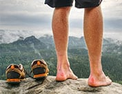 Image of person standing on mountain barefoot overlooking mountains