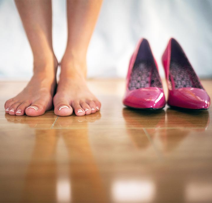 image of womans feet next to high heels