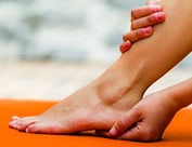 Image of person holding ankle and heel suffering from heel pain