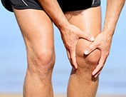 Image of person bent over in shorts holding knee suffering from knee pain