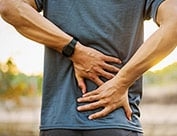 Image of person holding lower back suffering from lower back pain