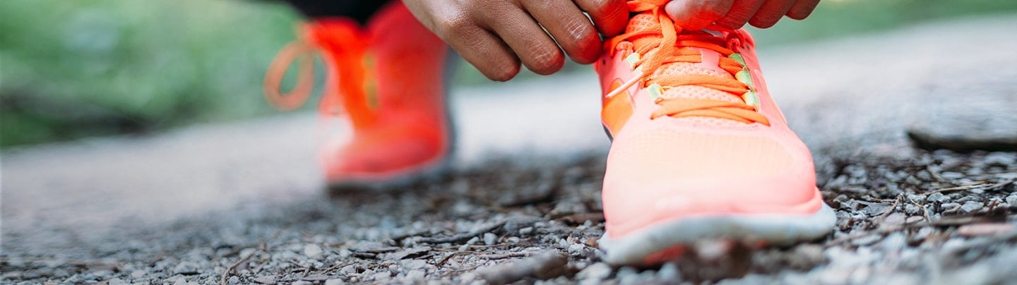 Image of a person leaned over tying  jogging shoes.