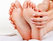 Image of person rubbing bottom of feet from dry and cracked skin