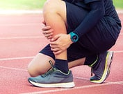 Picture of runner knelt down in pain from shin splints
