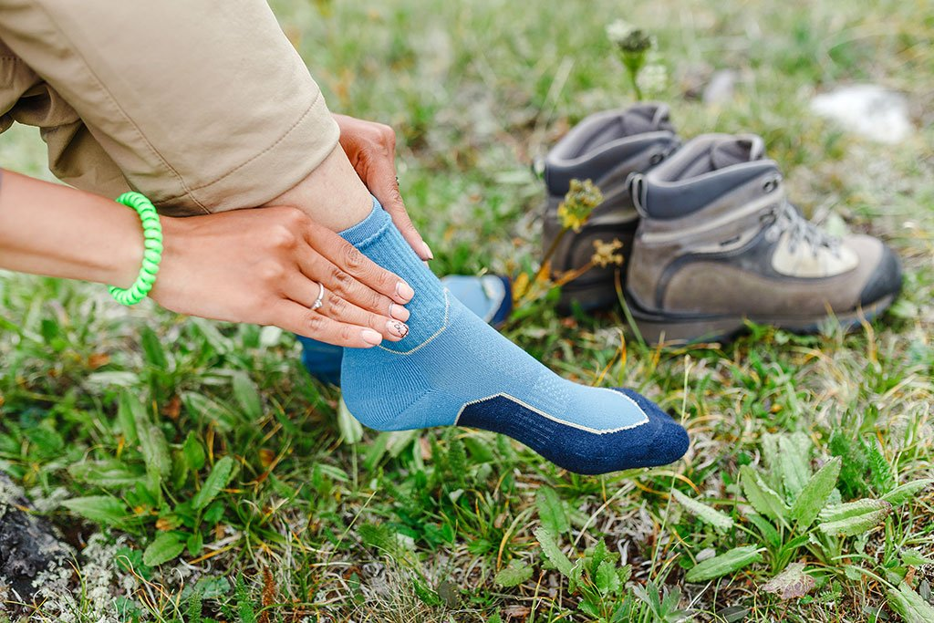 image of woman outside putting on sweat absorbing socks