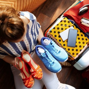 image of woman packing shoes in suitcase