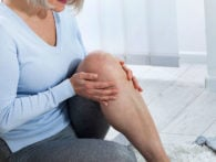 image of woman sitting on floor grabbing her knee