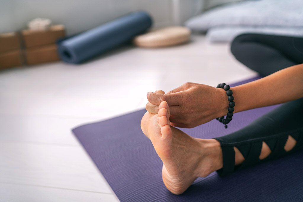image of woman doing a yoga toe hold stretch