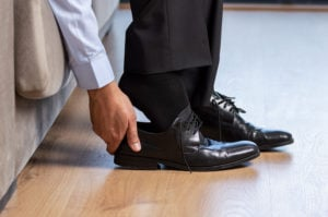 image of man putting on dress shoes