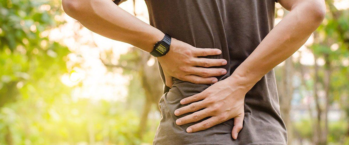 image of man holding his lower back